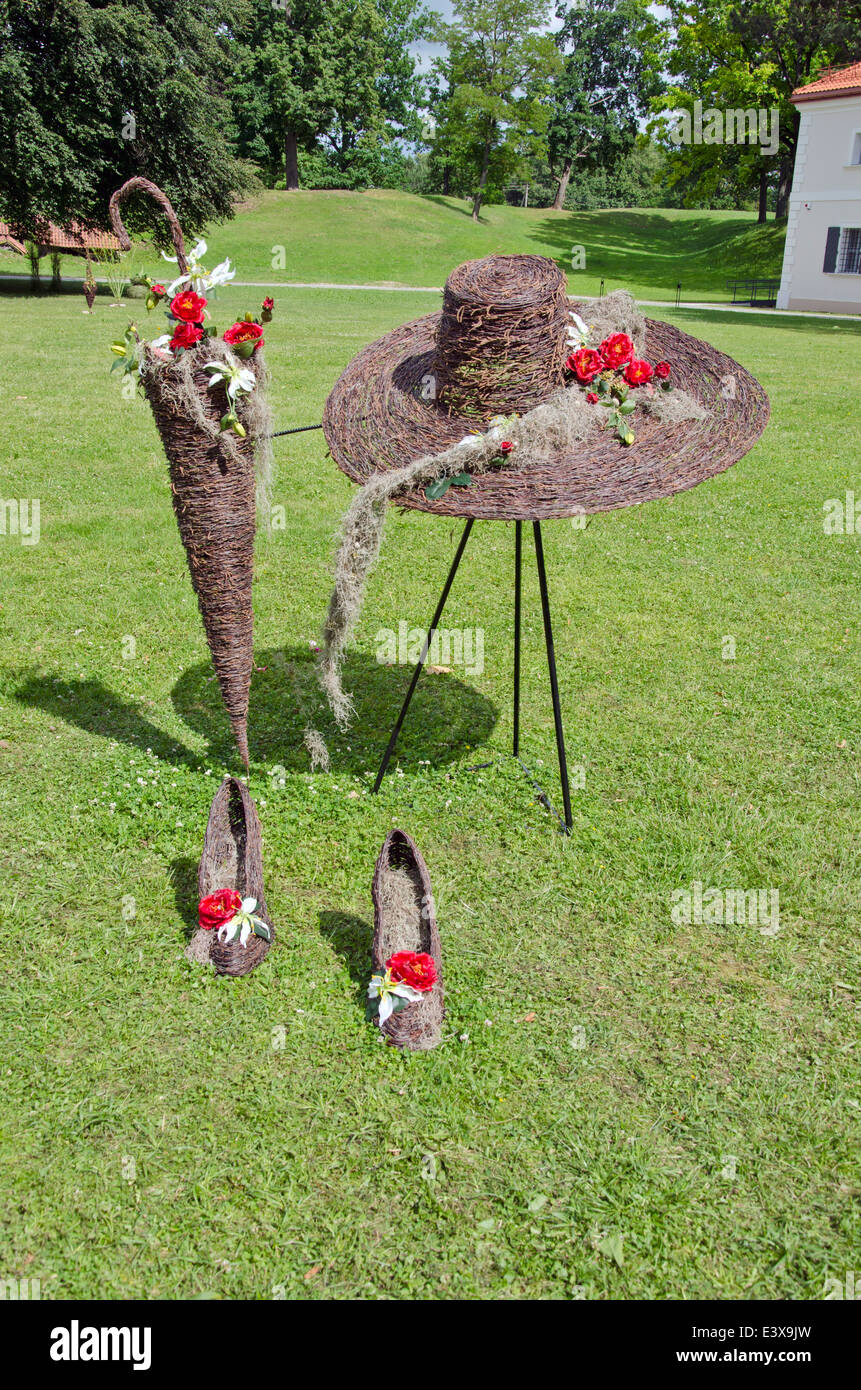 wicker beautiful florist objects in city park on grass. Wicker hat,stiletto and umbrella - Stock Image