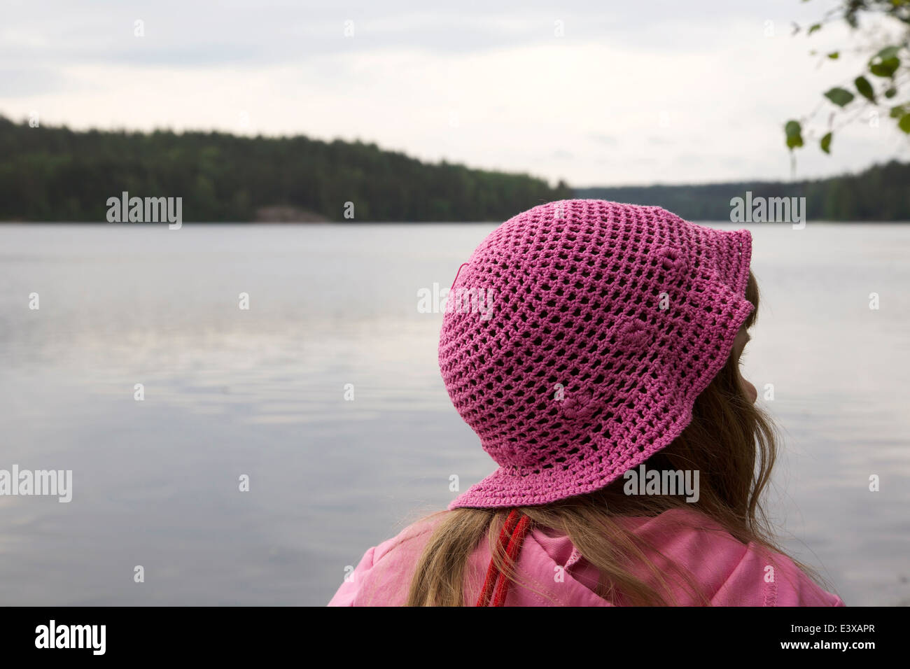 Girl looking at a calm lake scenery - Stock Image
