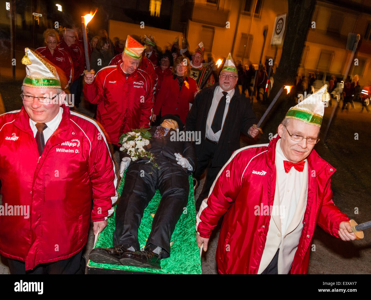German carnival revelers in good mood carry the deceased Bacchus dummy to his cremation burial at the end of the - Stock Image