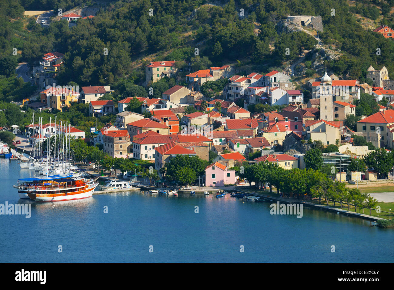 Townscape with sailing ship in the foreground, River Krka, Skradin, Dalmatia, Croatia - Stock Image
