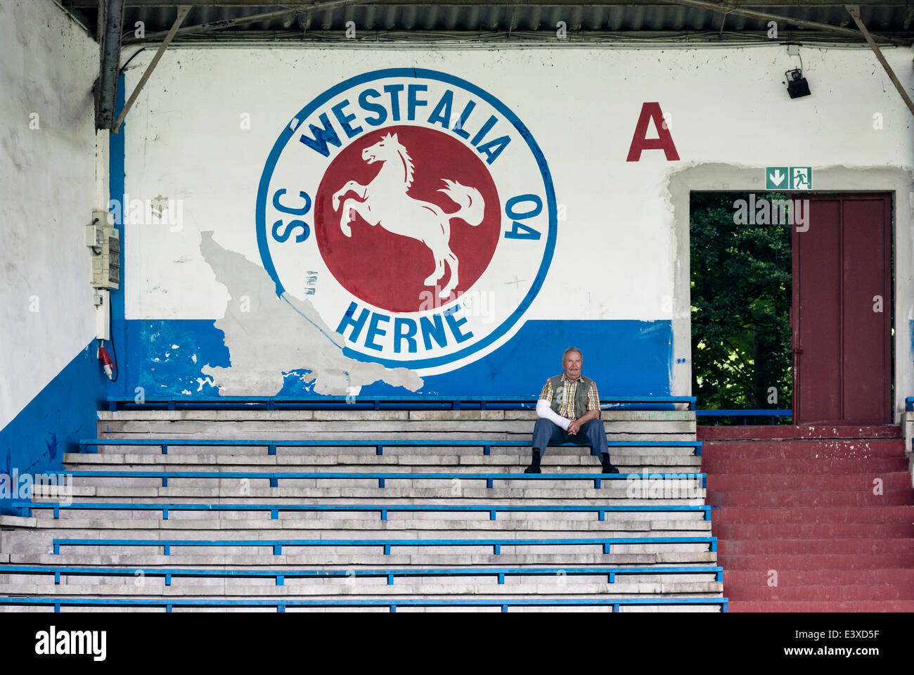 A single spectator sits on the derelict stands of the formerly renowned football club Westfalia Herne. - Stock Image