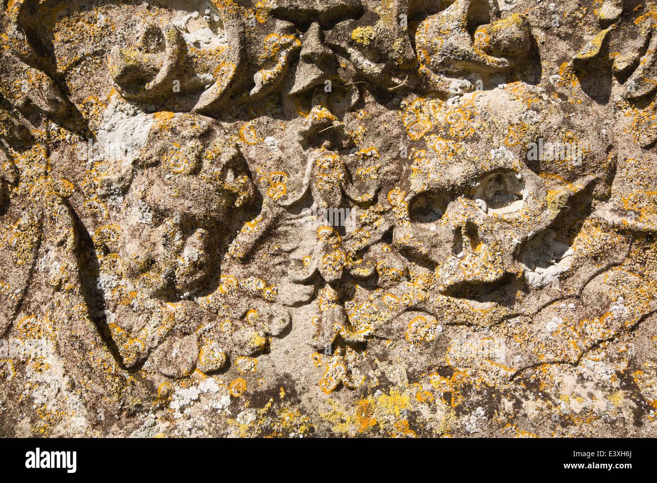 UK England, Suffolk, Lavenham, Parish Churchyard, lichen covered skull and cherub motif on gravestone - Stock Image
