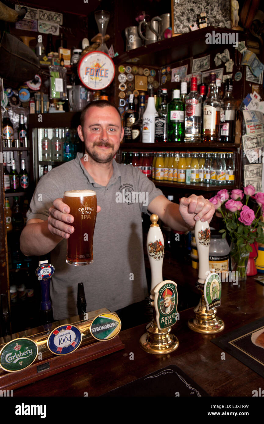 UK England, Suffolk, Bury St Edmunds, holding pint of IPA in Nutshell, Britain's smallest pub - Stock Image