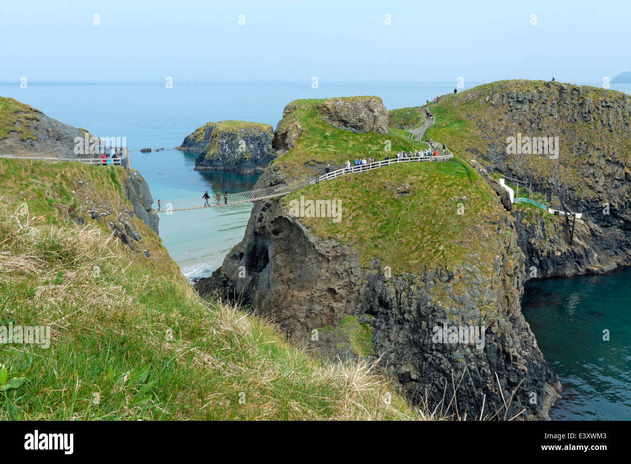 View on Carrick-a-Rede island and the famous Carrick-a-Rede rope bridge near Ballintoy in County Antrim, Northern - Stock Image