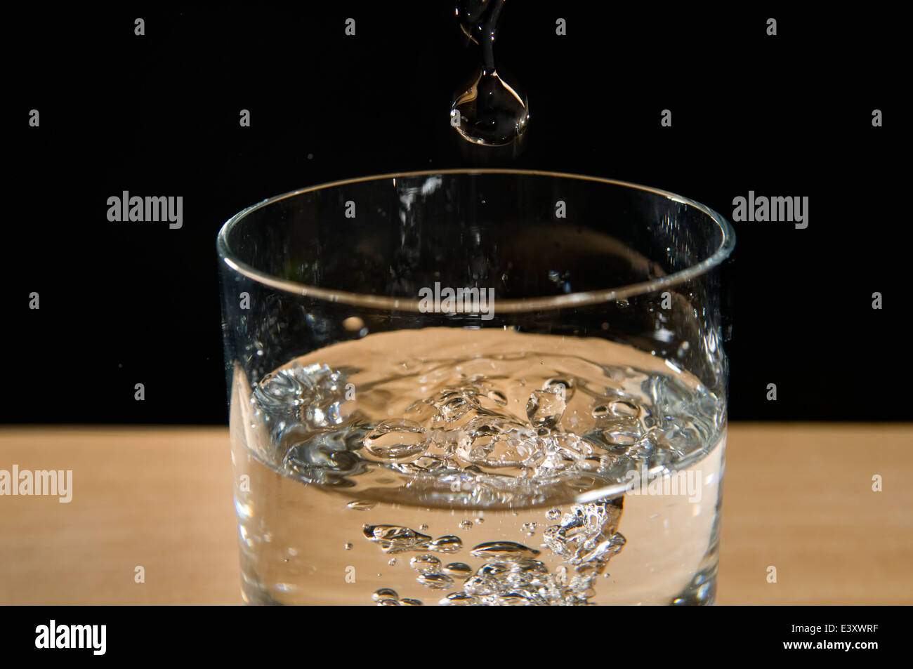 Water droplet in glass of fresh water against black background - Stock Image