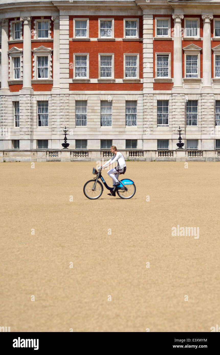 London, England, UK. Woman riding a 'Boris Bike' in Horse Guards Parade. (Building in focus - cyclist slightly - Stock Image