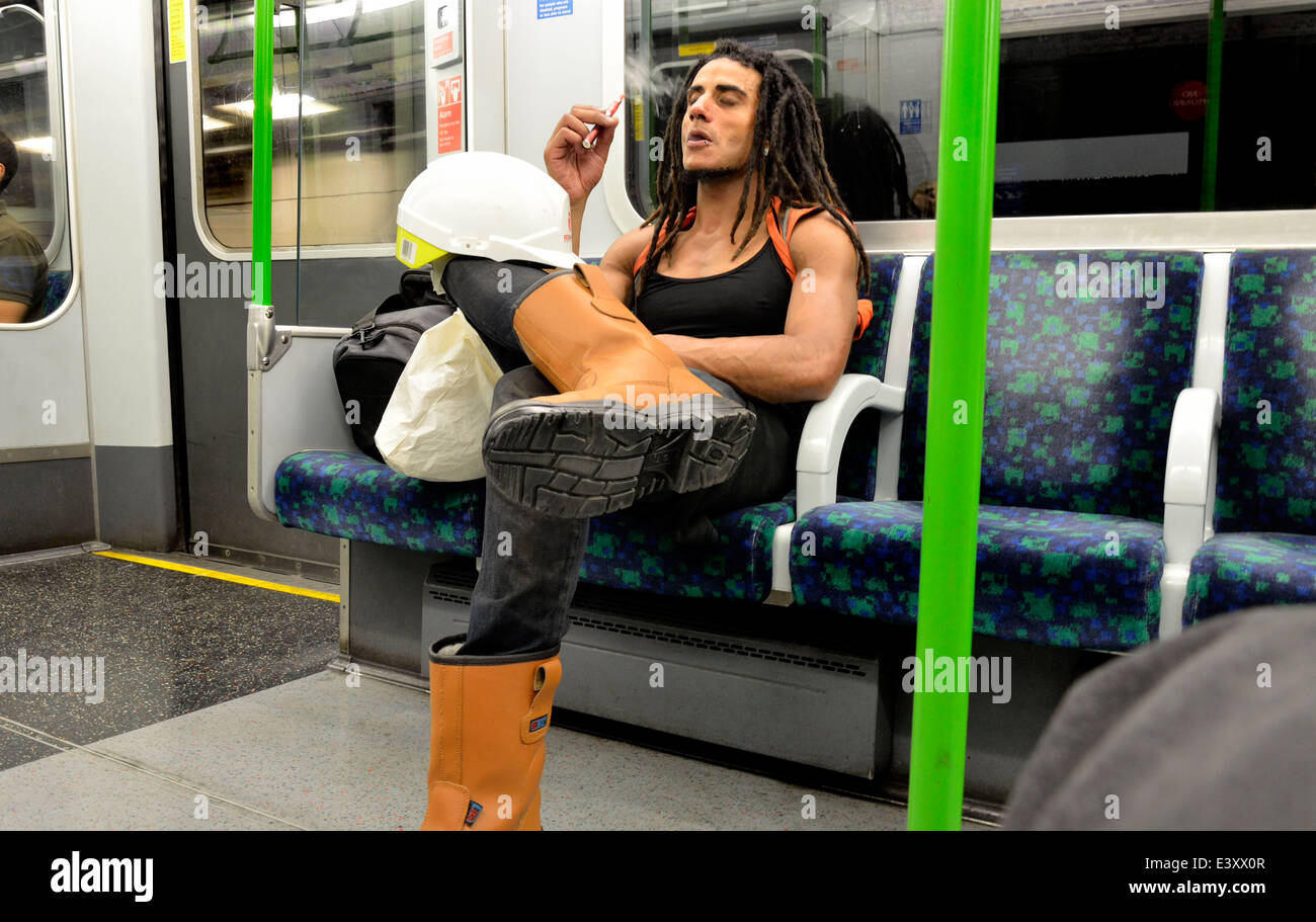 London, England, UK. Man smoking an e-cigarette on an underground train - Stock Image