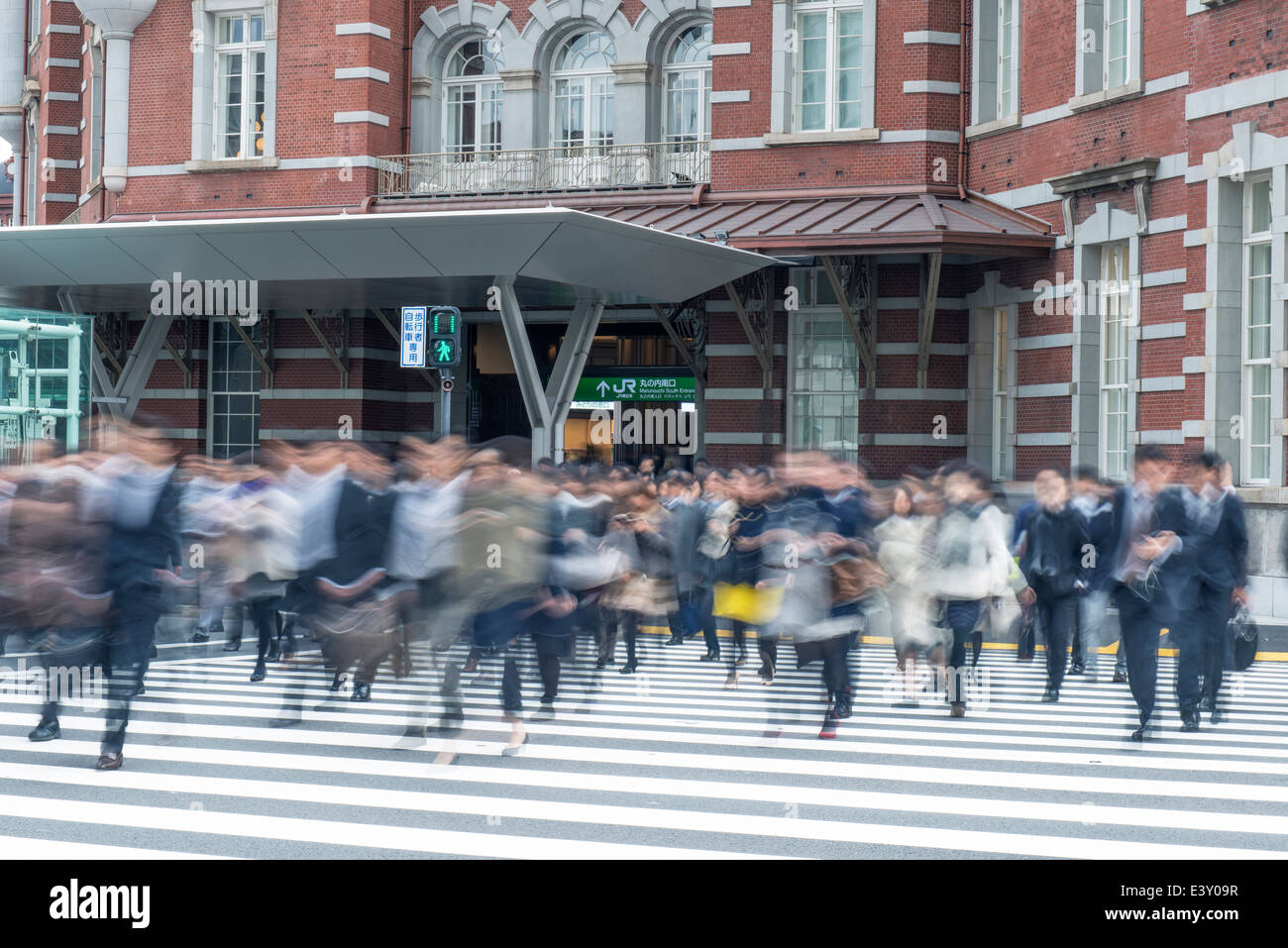 Blurred view of pedestrians crossing city street - Stock Image