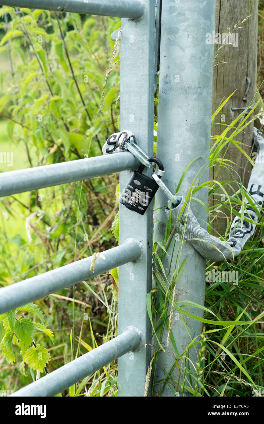 Combination padlock and chain on galvanized steel metal gate and post Stock Photo