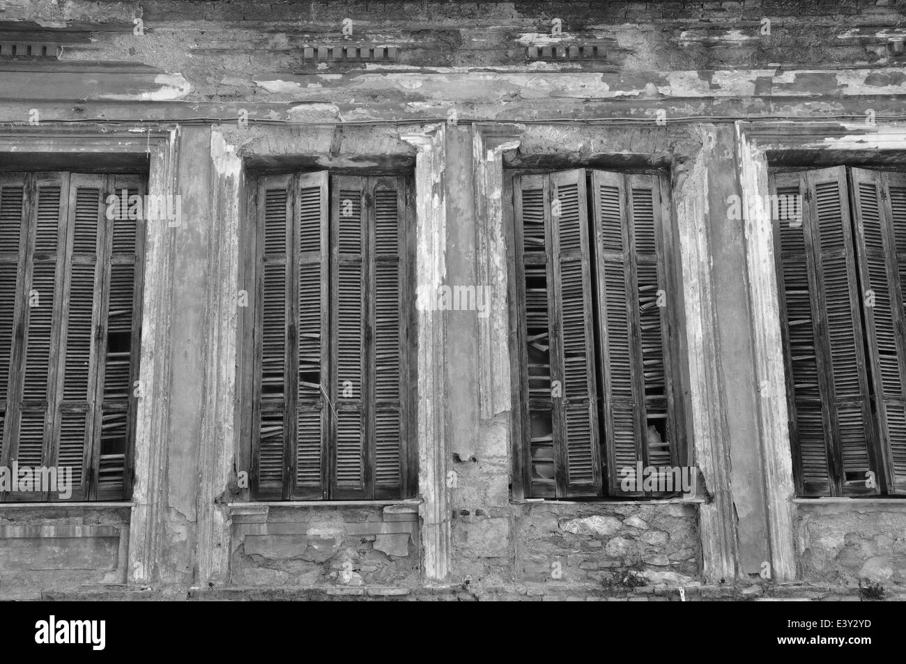Broken wooden window shutters and textured wall of an abandoned house. Urban decay black and white. - Stock Image