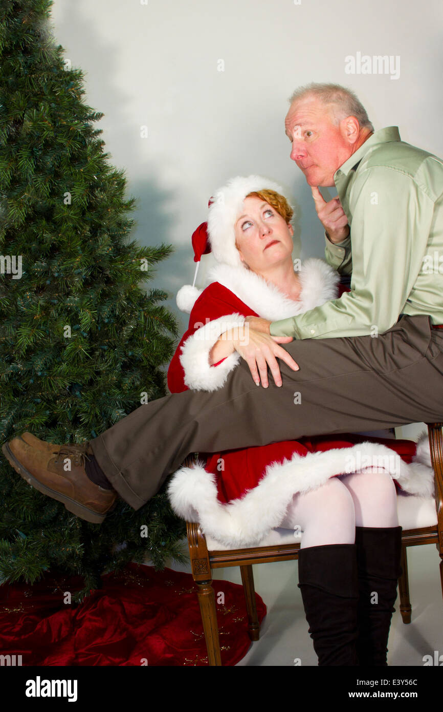 A Wish For Christmas.Man Sitting On The Lap Of A Woman Dressed As Mrs Claus