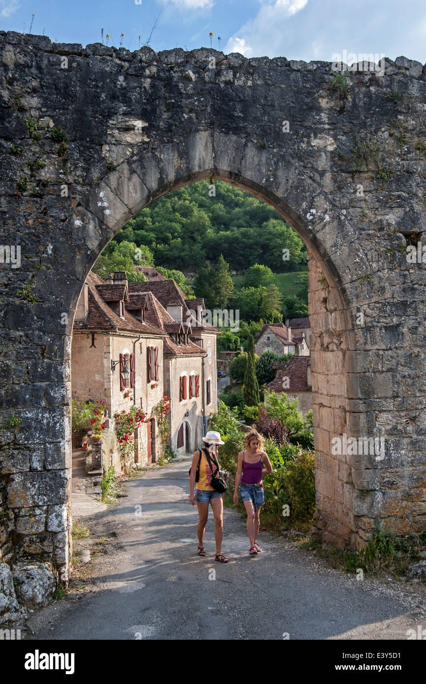 Tourists walking through town gate at the medieval village Saint-Cirq-Lapopie, Lot, Quercy, Midi-Pyrénées, - Stock Image
