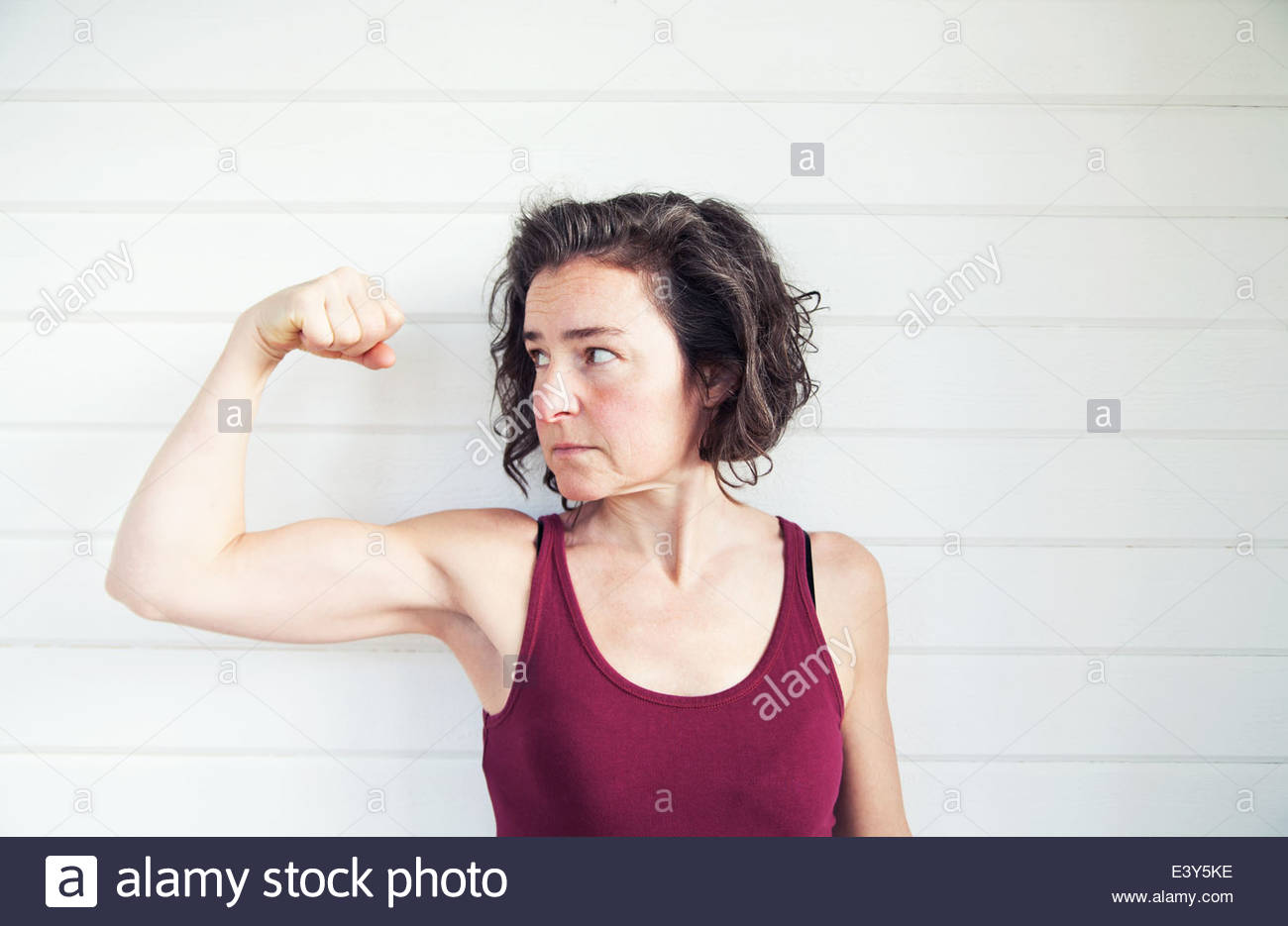 Portrait of determined mature woman flexing arm muscles - Stock Image