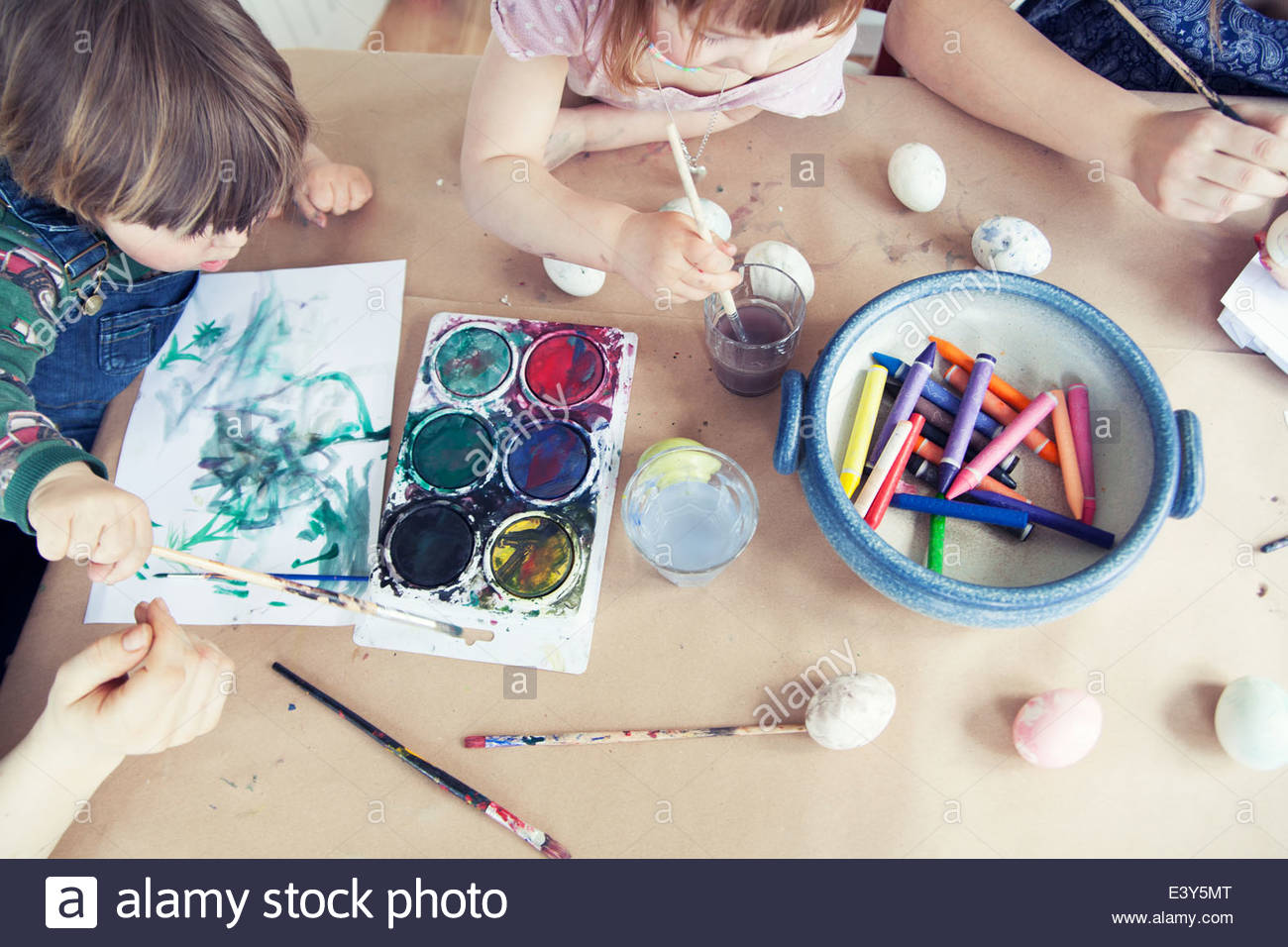 Overhead cropped view of family painting easter eggs - Stock Image