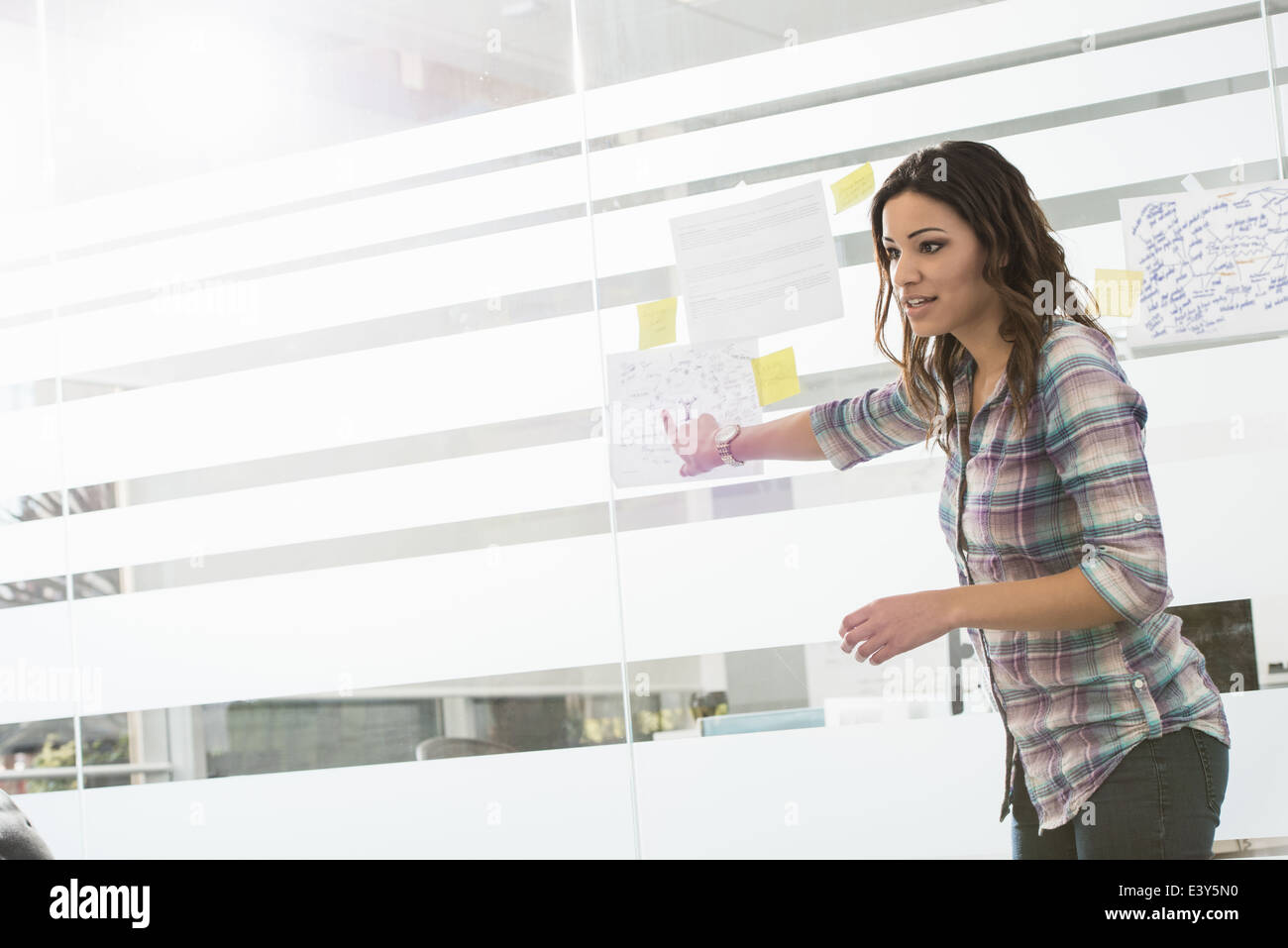 Young businesswoman presenting ideas on office window - Stock Image
