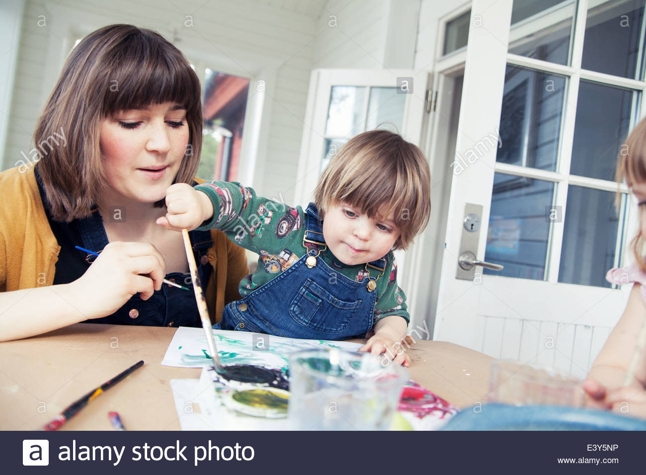 Mother and two children painting in dining room - Stock Image