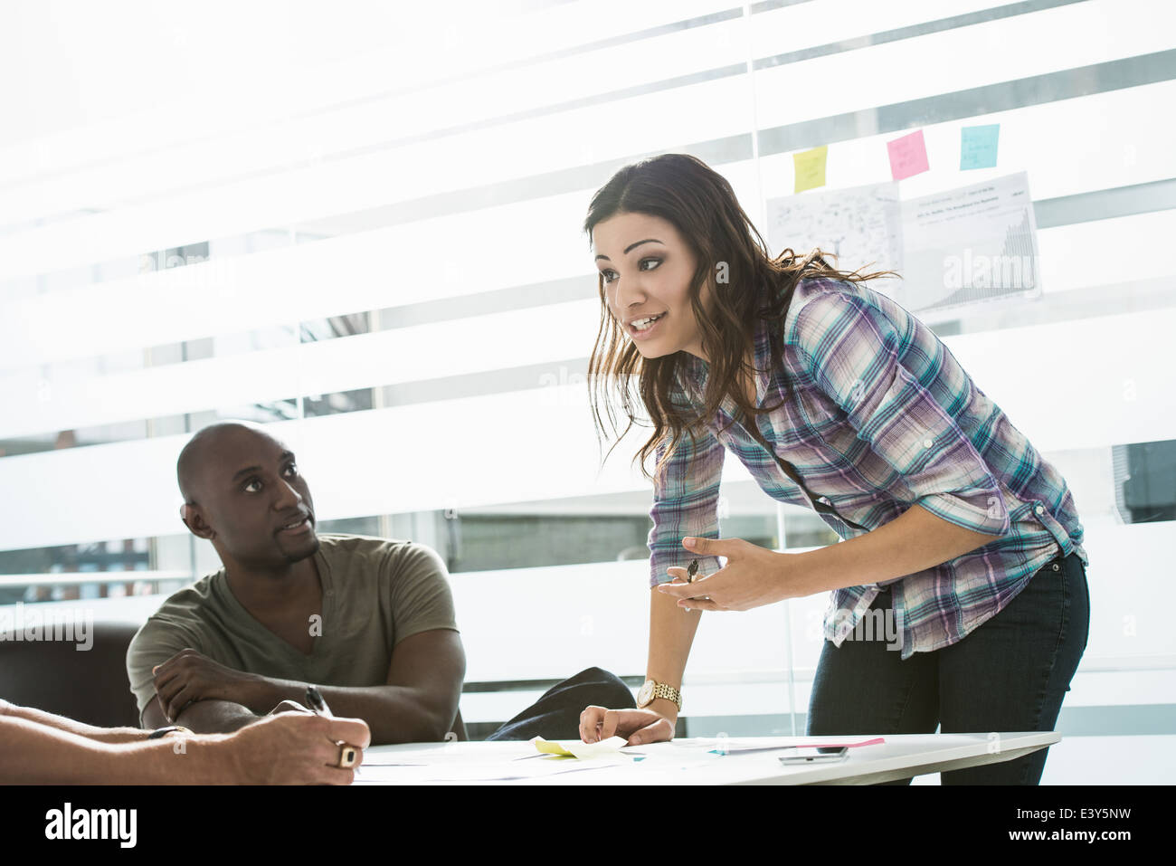 Businesswoman explaining ideas to male colleagues in office - Stock Image