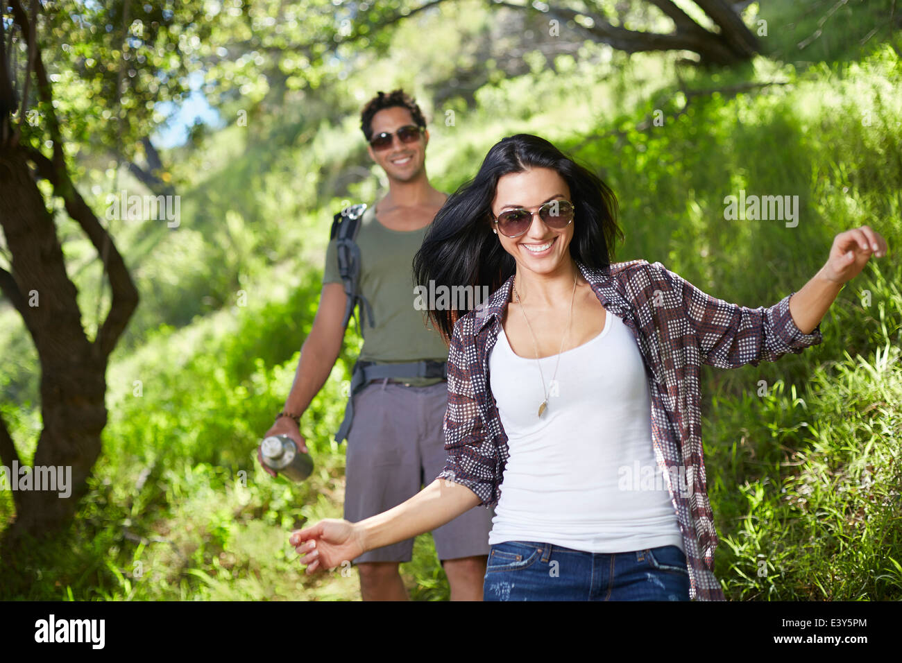 Smiling couple walking in woodlands - Stock Image