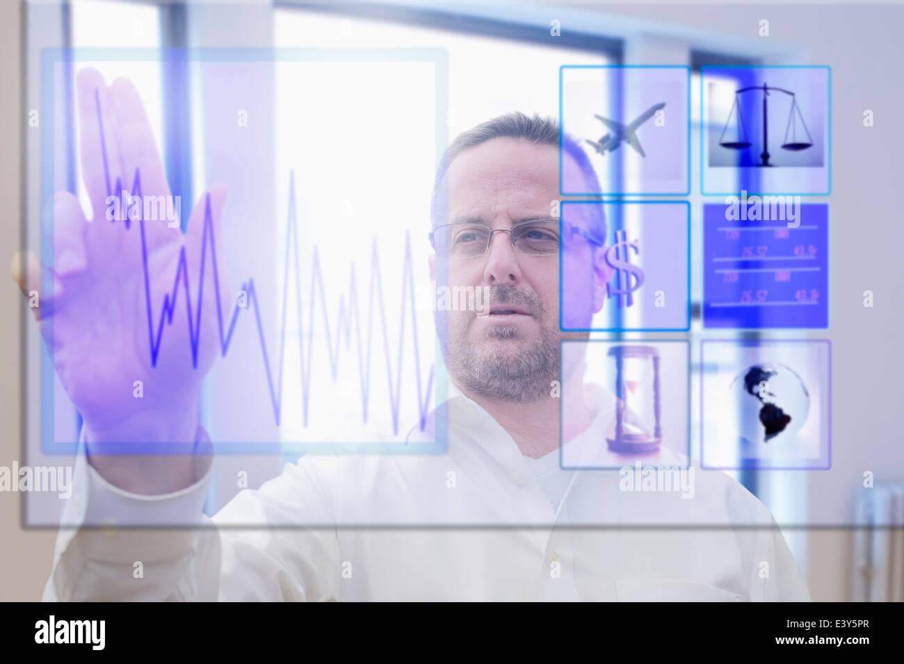 Mature man using interactive computer touchscreen - Stock Image