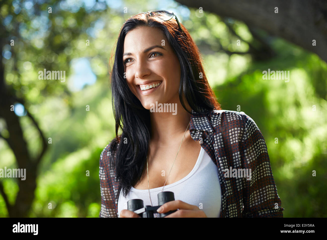 Mid adult woman birdwatcher in forest - Stock Image