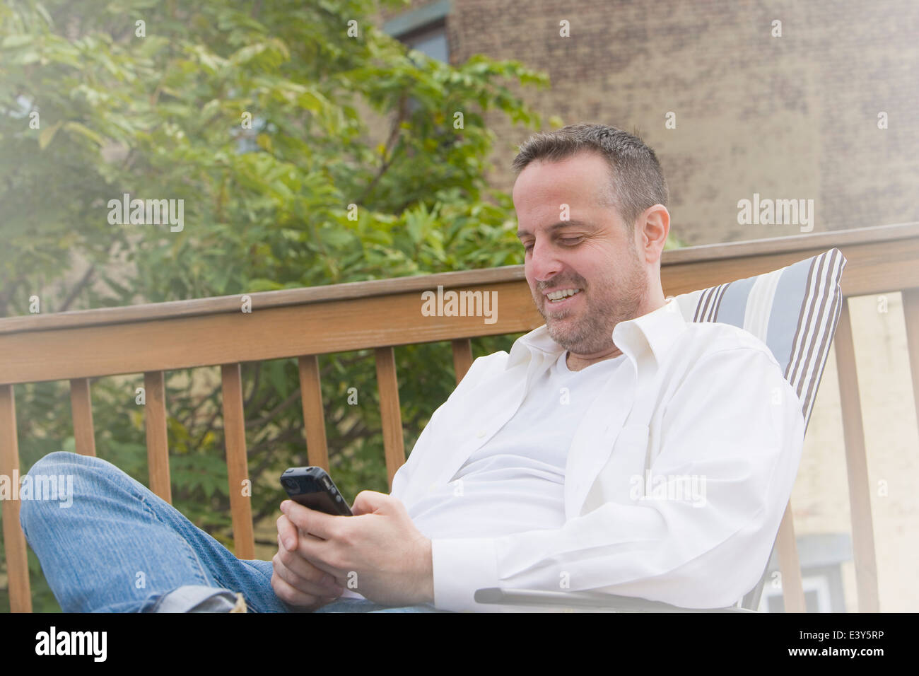 Mature man in garden deck chair texting on smartphone - Stock Image