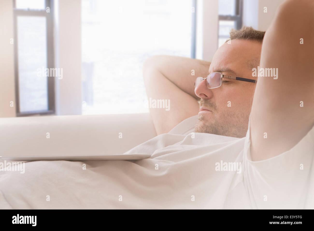 Close up of mature man asleep on sofa - Stock Image