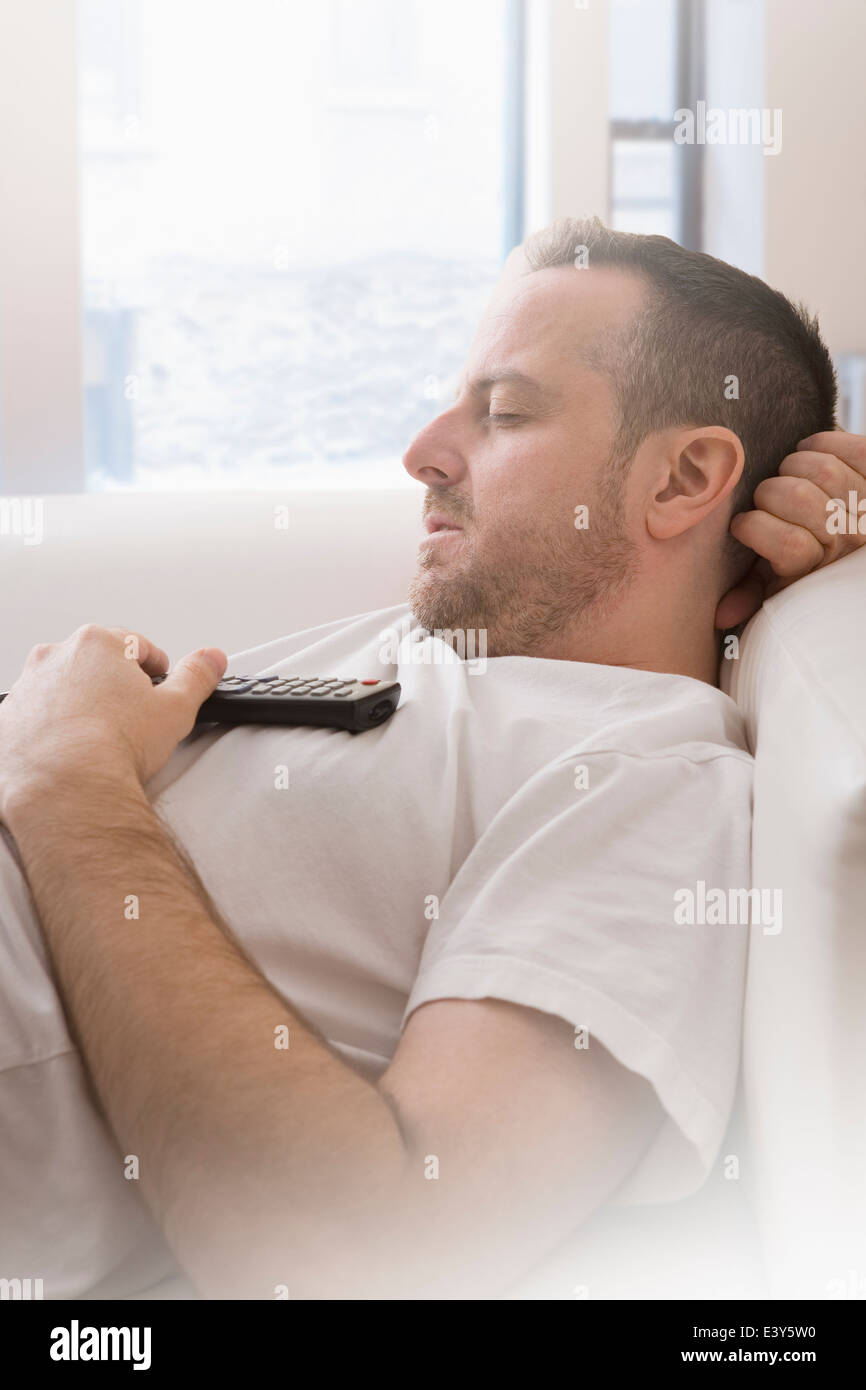 Mature man with remote control asleep on sofa - Stock Image