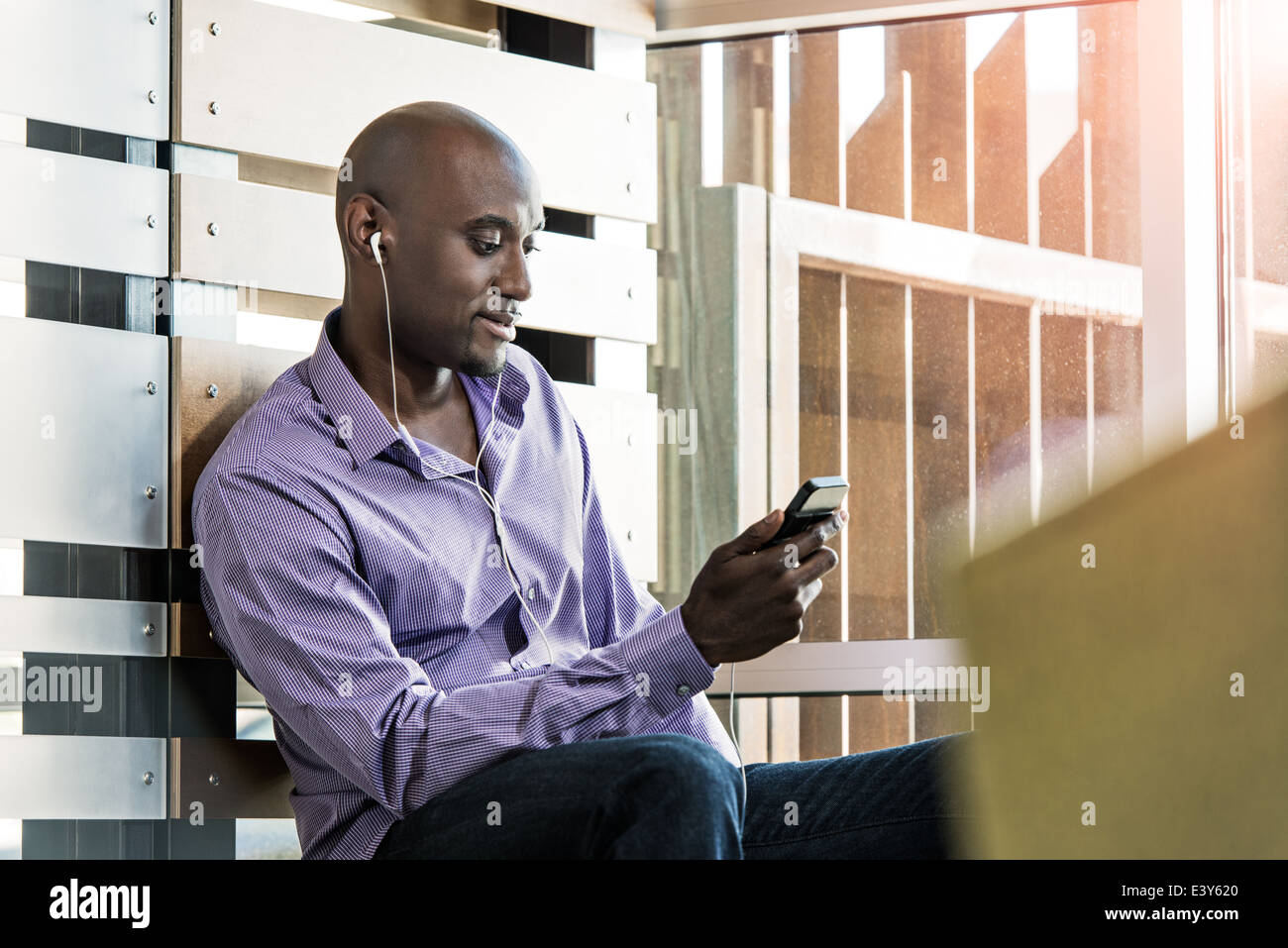 Male office worker listening to smartphone earphones in office - Stock Image