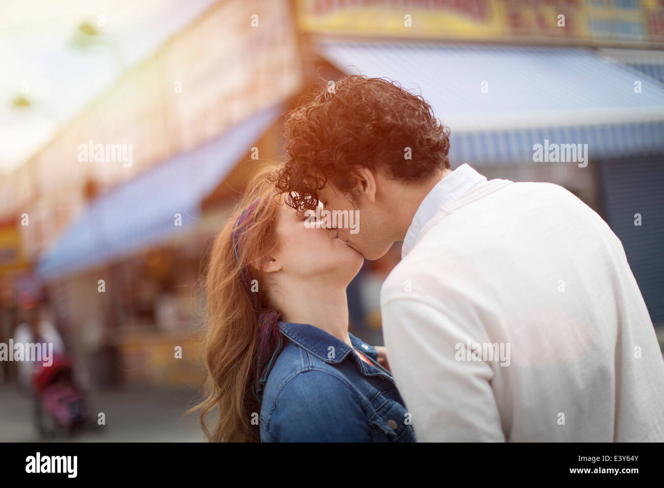 Romantic couple kissing at amusement park - Stock Image