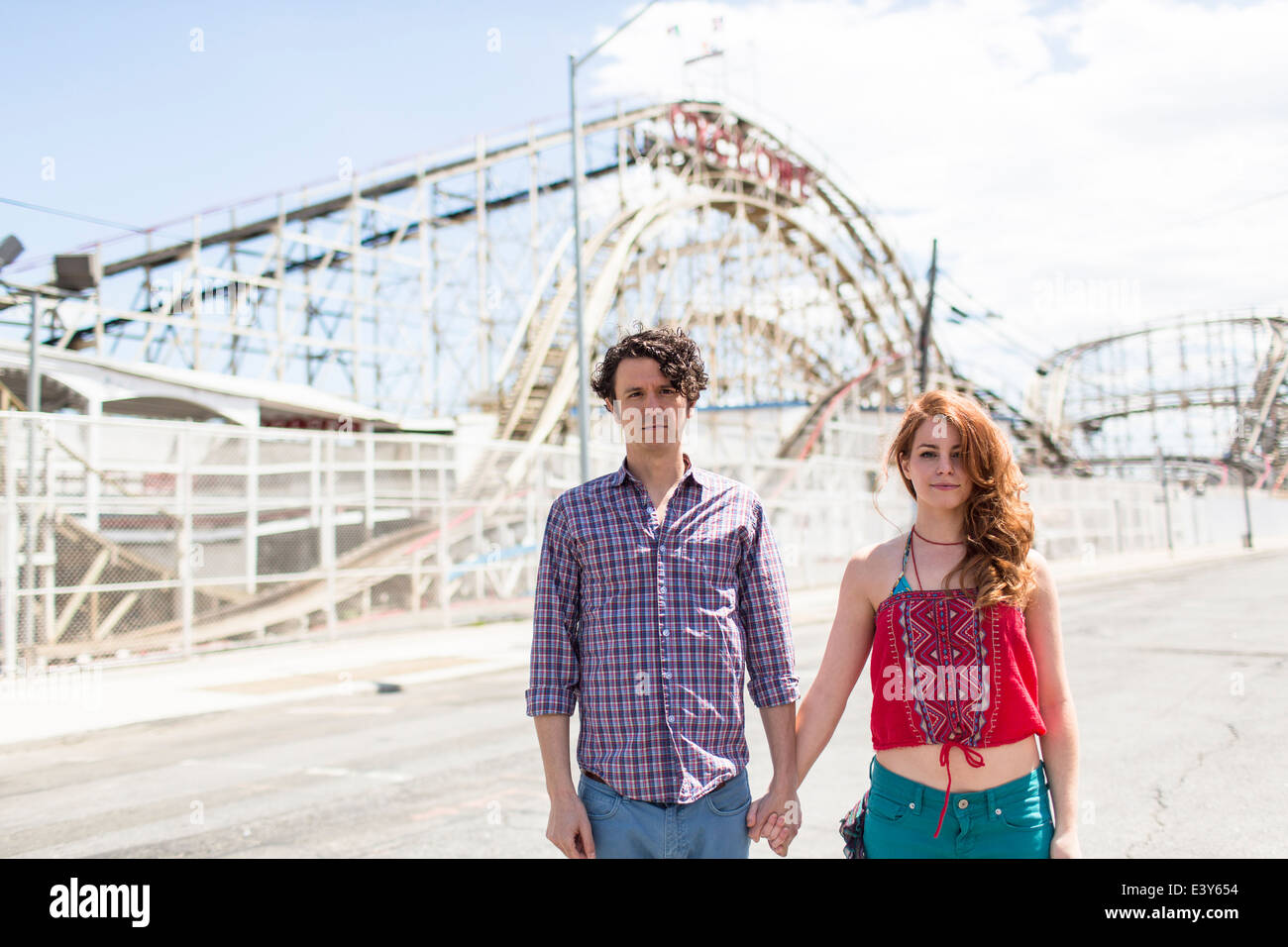 Portrait of couple with blank expressions at amusement park - Stock Image