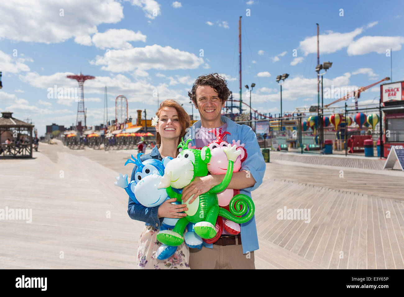 Portrait of couple with inflatable monkeys at amusement park - Stock Image