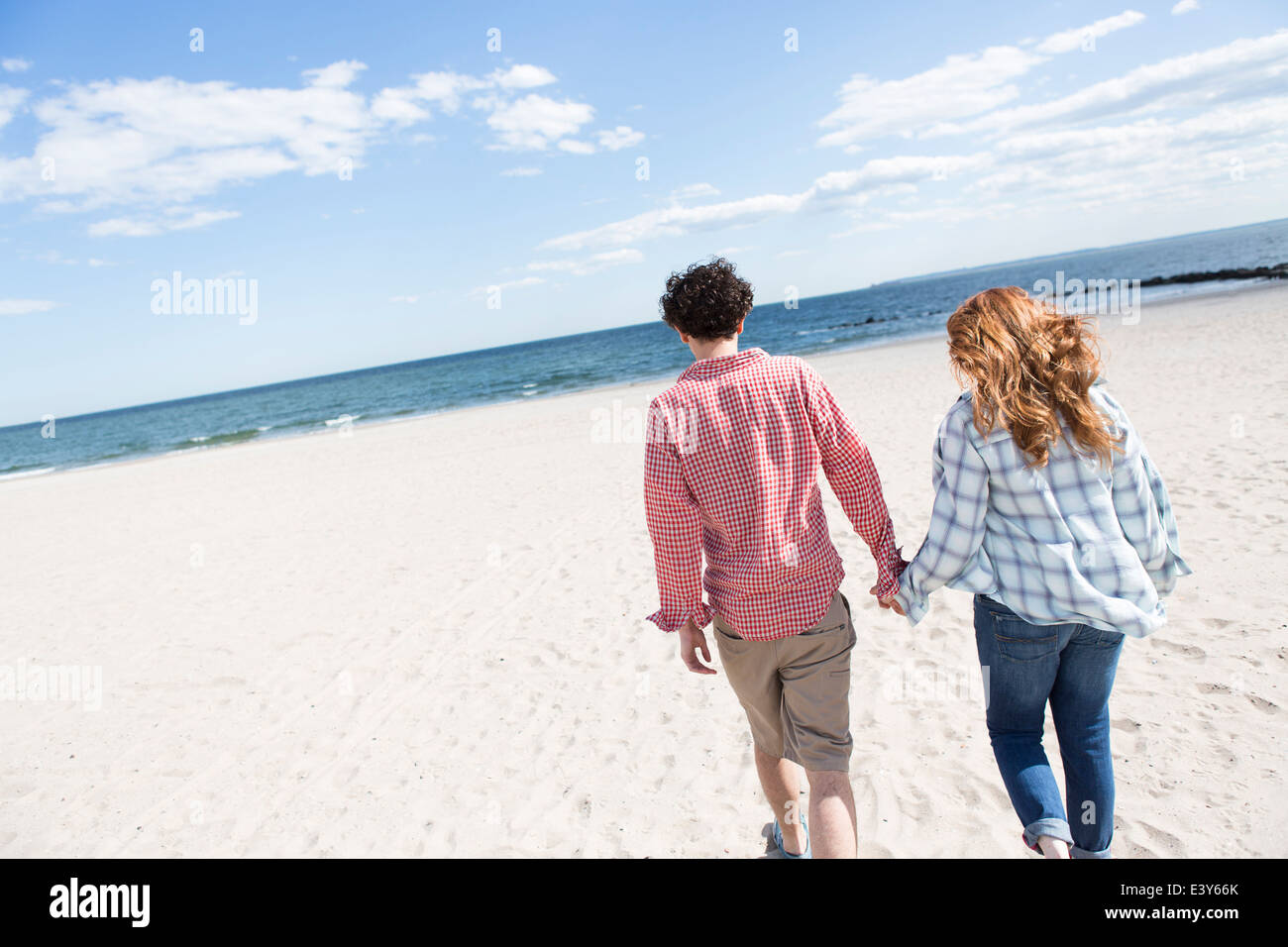 Romantic couple strolling hand in hand on beach - Stock Image