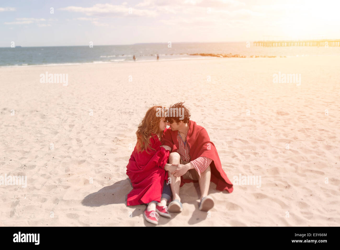 Romantic couple wrapped in blankets at beach Stock Photo