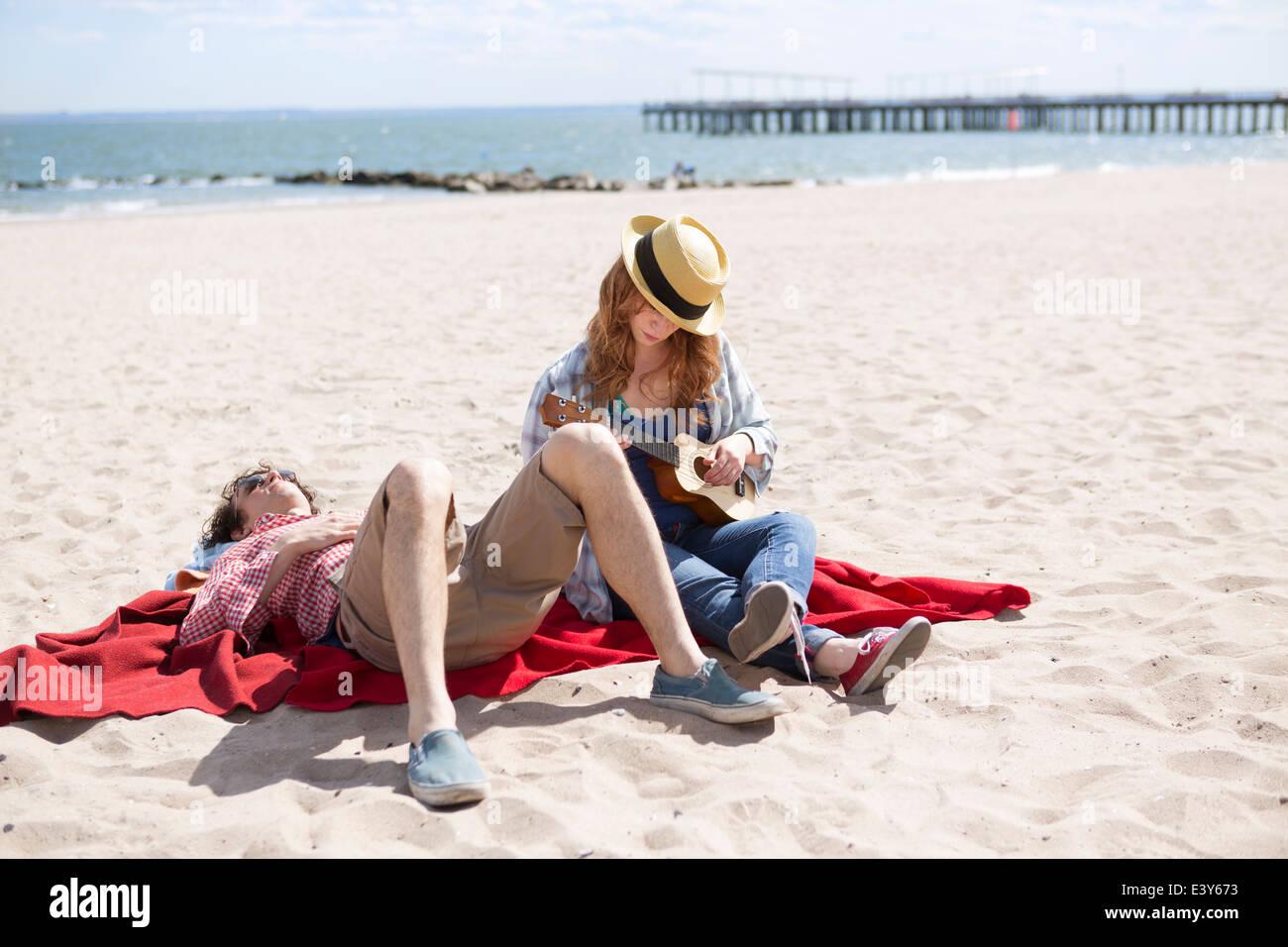 Couple sunbathing and playing ukulele on beach - Stock Image