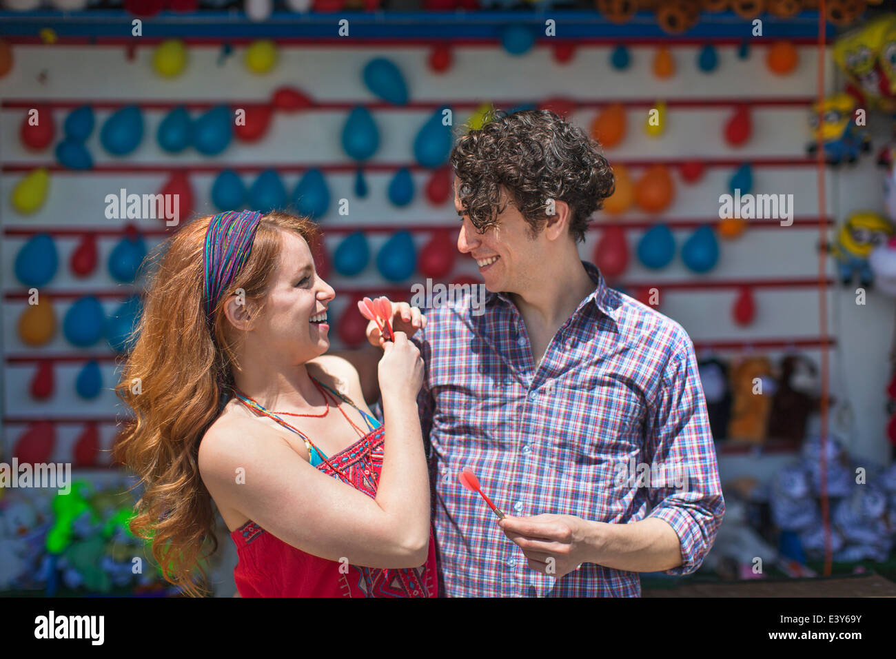 Couple with darts at fairground stall - Stock Image