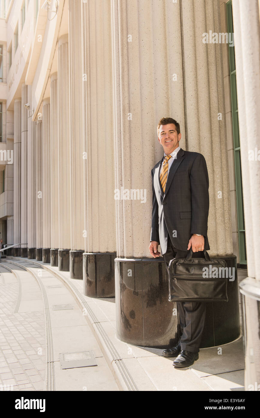 Portrait of business lawyer with briefcase outside courthouse - Stock Image