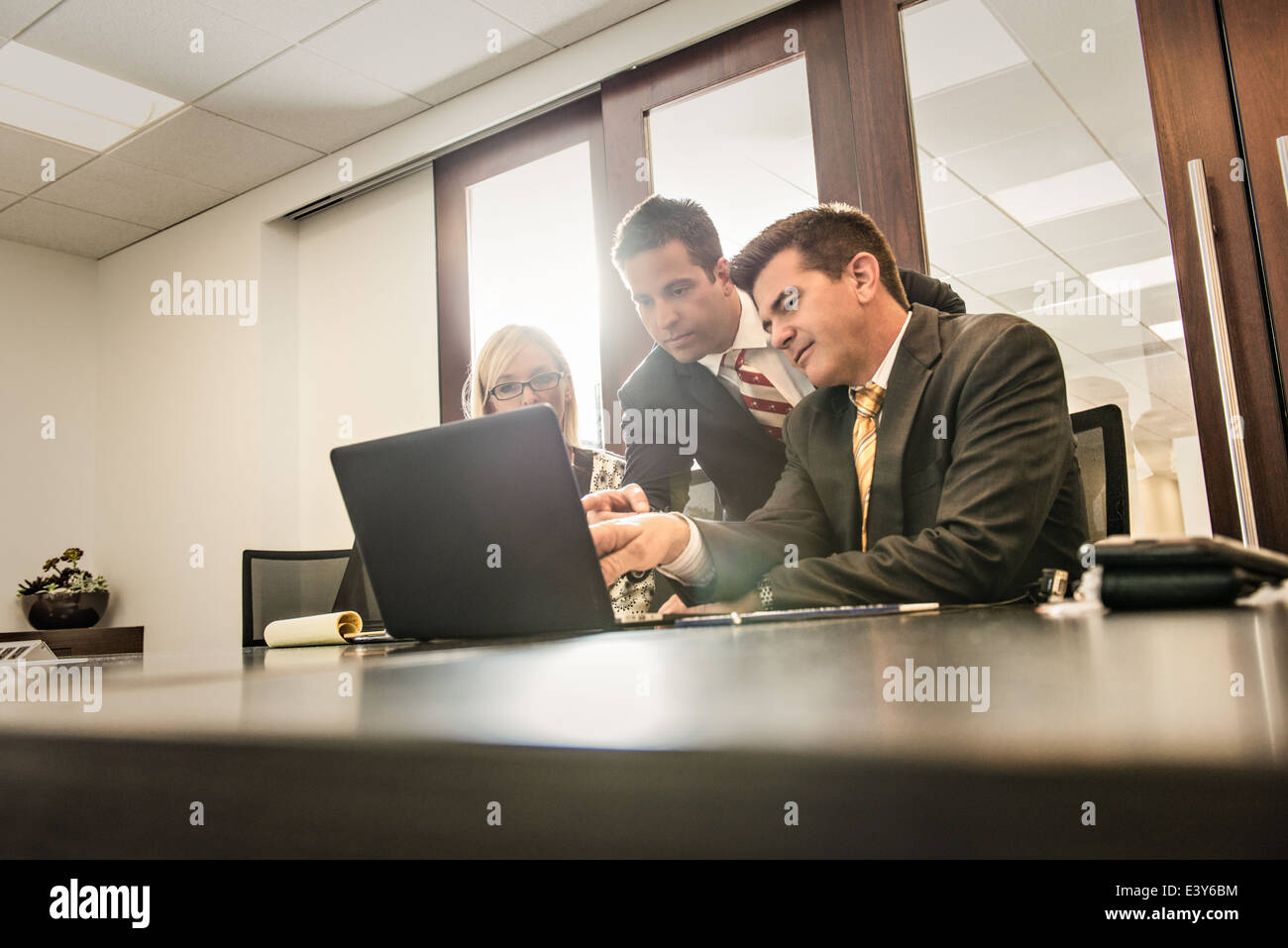 Three business lawyers having a planning meeting in office - Stock Image