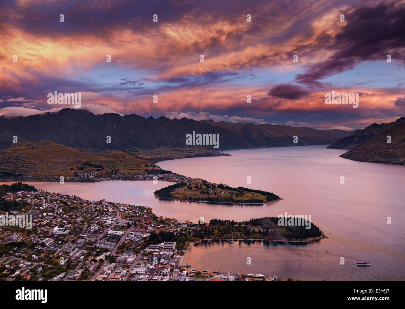 Queenstown cityscape with Wakatipu lake and Remarkables Mountains at sunset, New Zealand - Stock Image