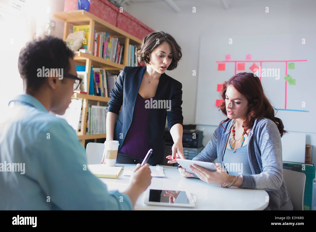 Young woman leading small meeting - Stock Image
