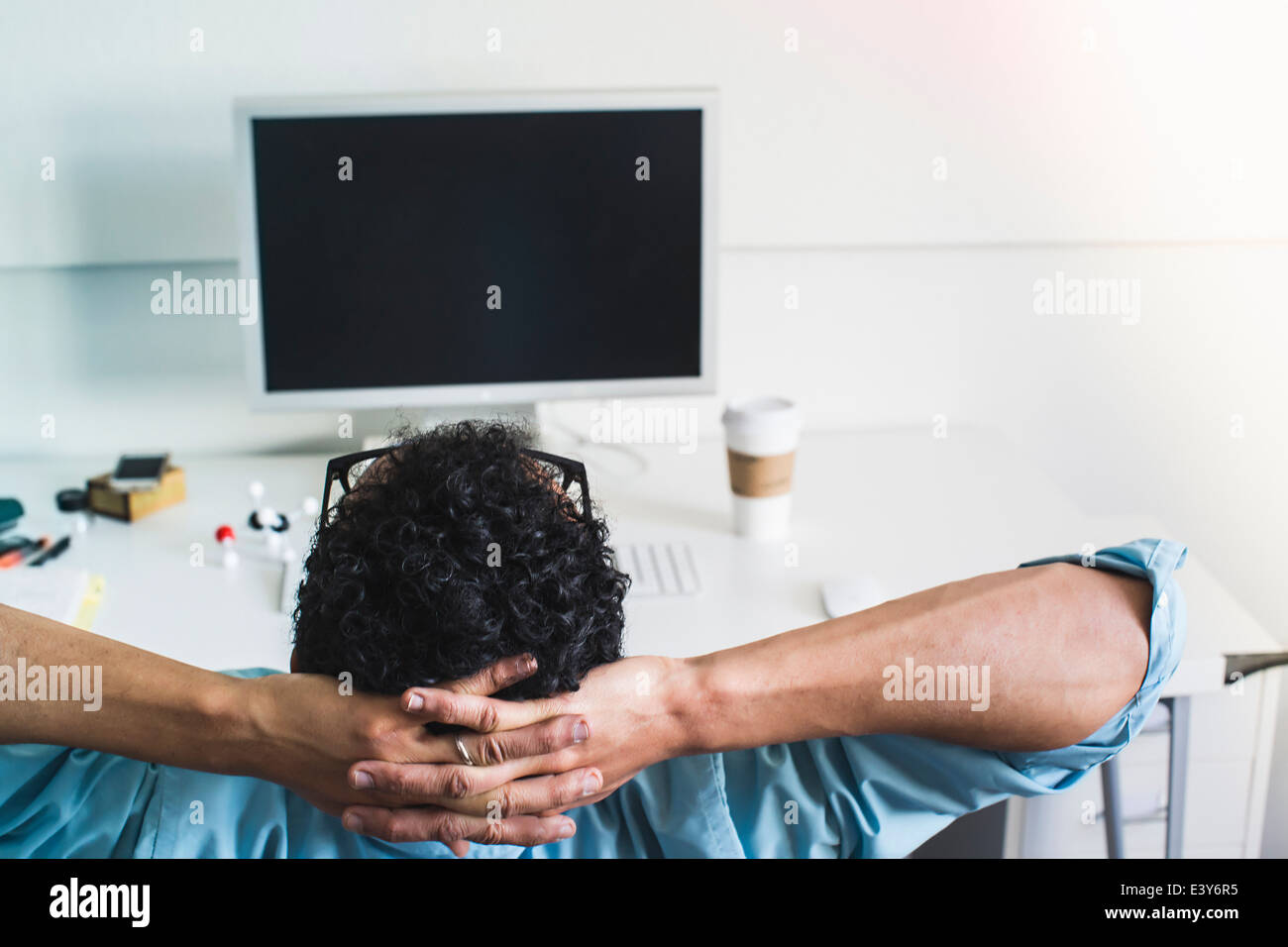 Young man taking break at office - Stock Image