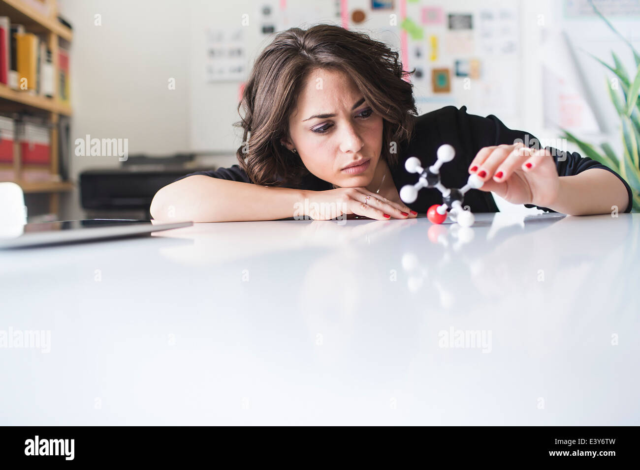 Young woman contemplating molecular model of Ethanol molecule - Stock Image