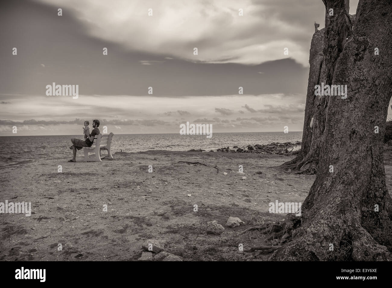 Black and white image of father and toddler daughter on beach bench - Stock Image