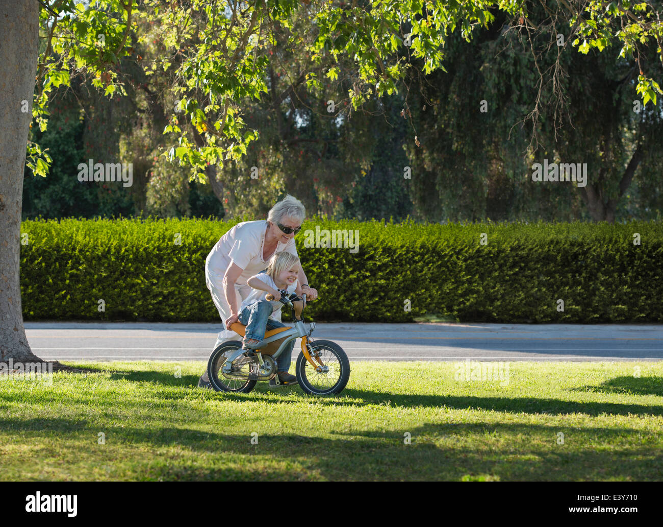 Three year old boy learning to cycle with grandmother in park - Stock Image