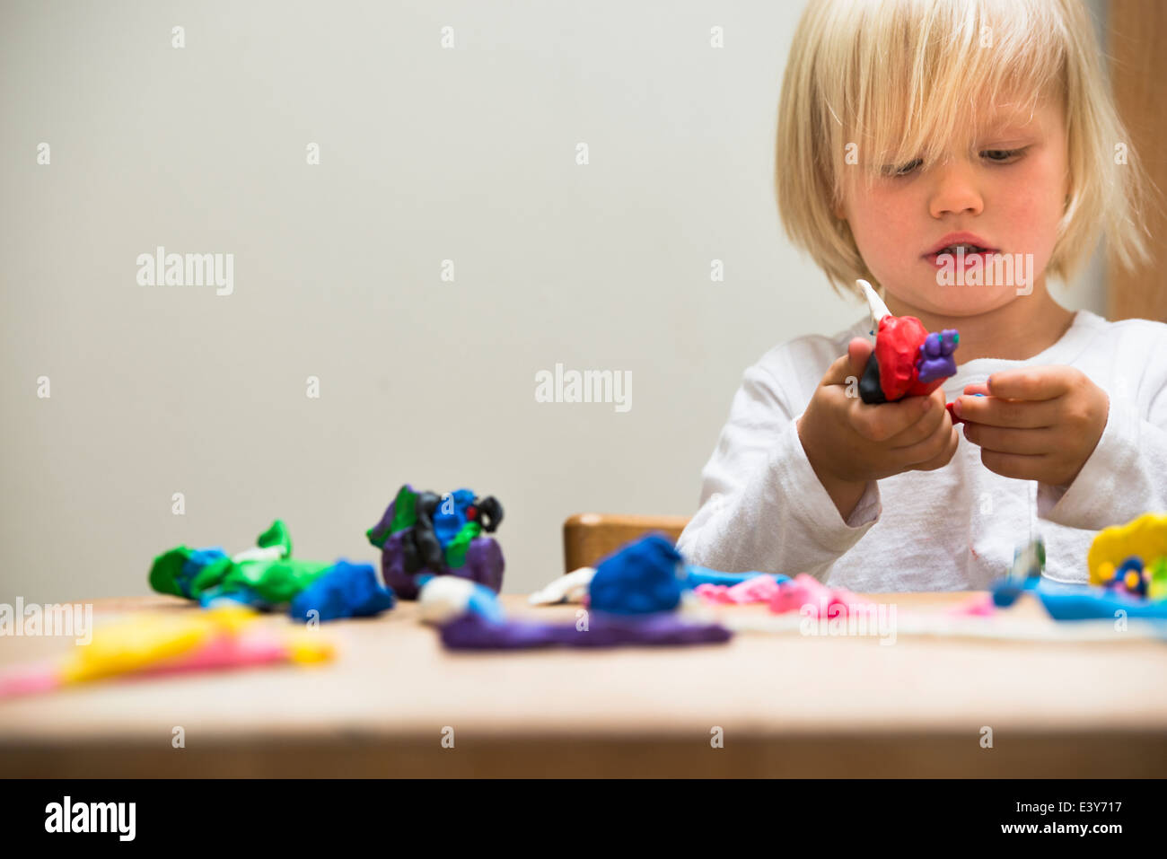 Three year old boy playing with modeling clay - Stock Image