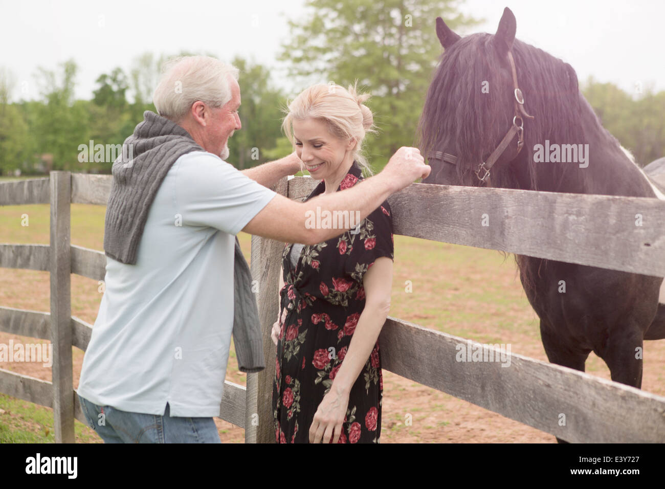 Horse watching mature couple over fence Stock Photo