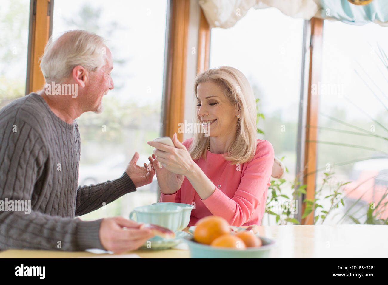 Mature couple chatting about text message on smartphone - Stock Image
