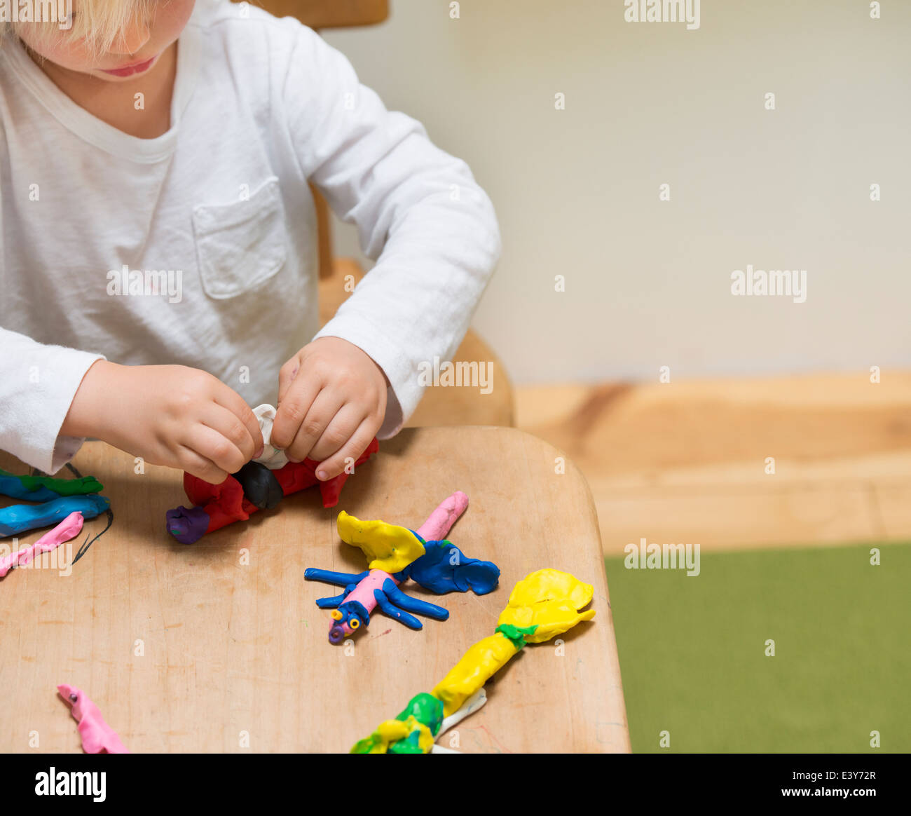 Cropped shot of three year old boy playing with modeling clay - Stock Image