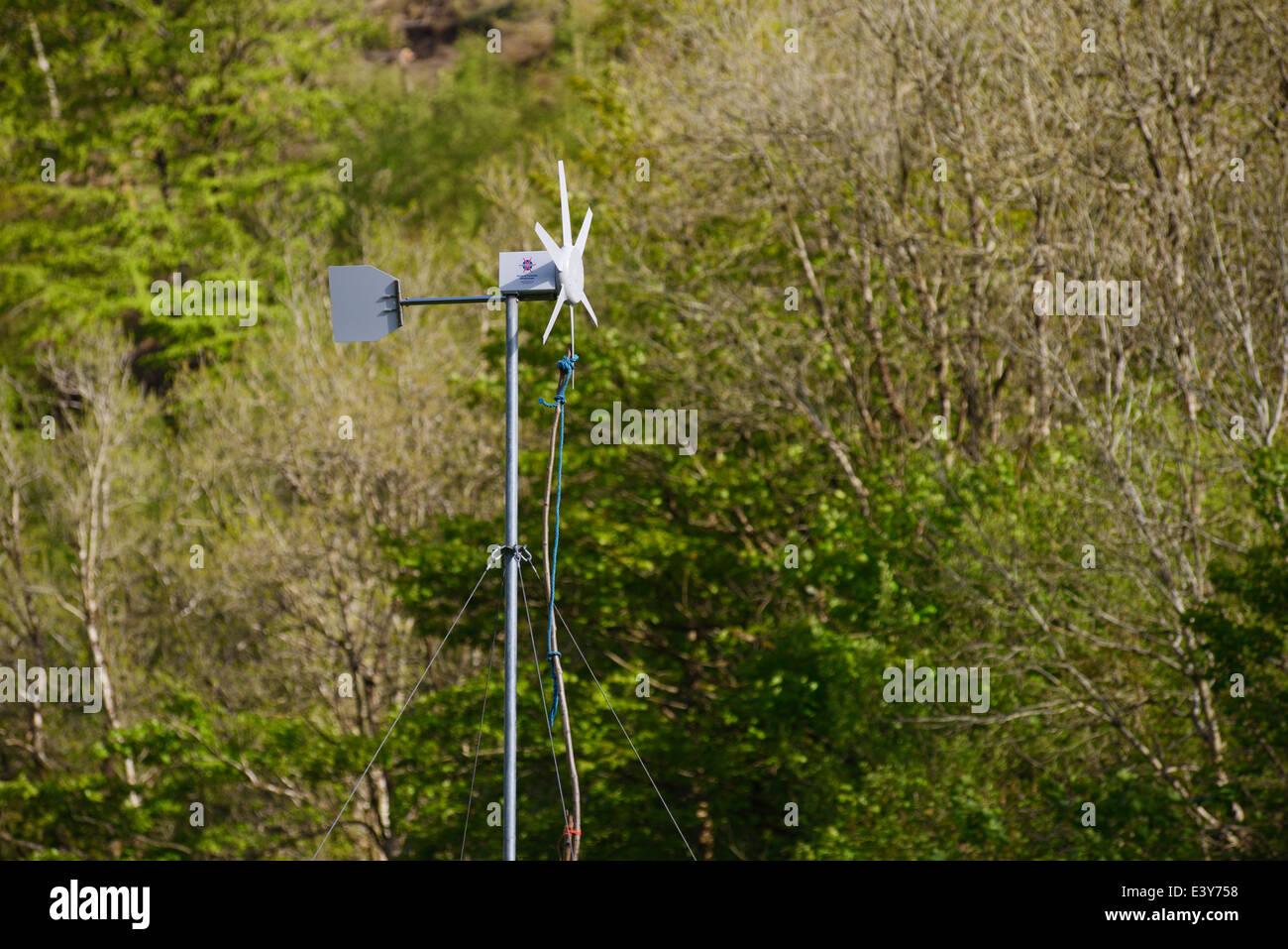 Small wind turbine, secured with a stick and rope for maintainance, Wales, UK. - Stock Image