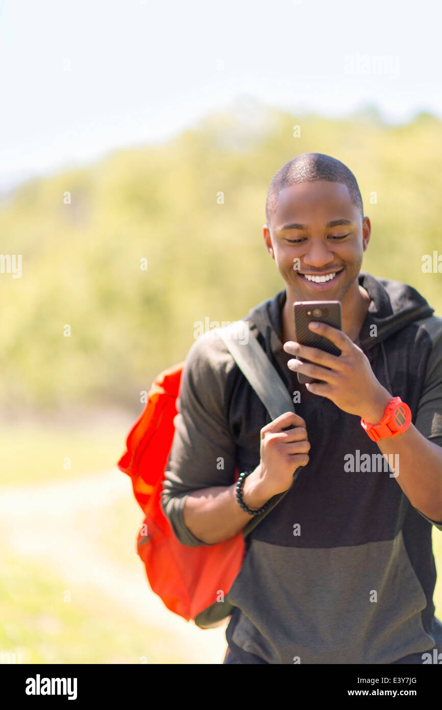 Young male hiker reading message on smartphone - Stock Image
