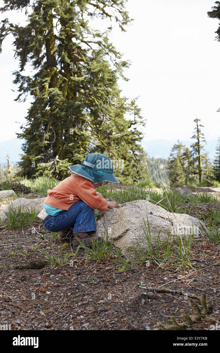 Toddler bending down to look at rock - Stock Image